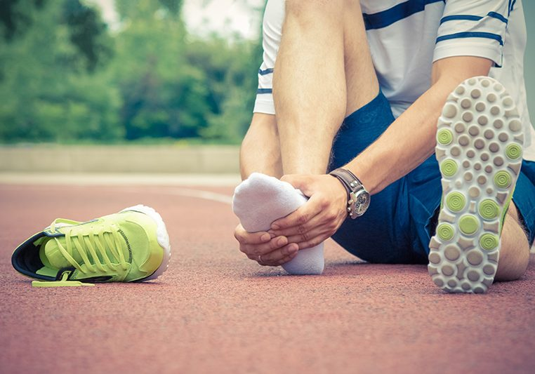 Jogger hands on foot. He is feeling pain as his ankle or foot is