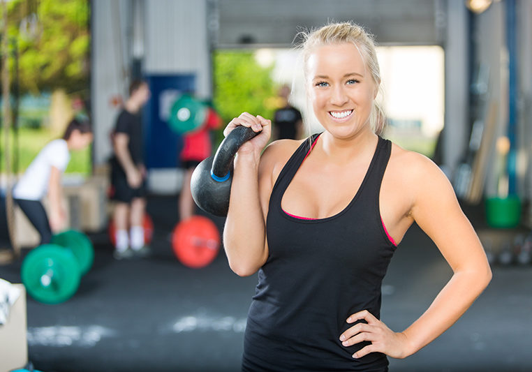 Portrait of happy female athlete lifting kettlebell at gym